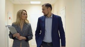 Affärskvinnan och en man promenerar korridoren och samtalet lager videofilmer