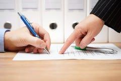 Affärskvinnan pekar var att underteckna på dokument, med docum Arkivbilder