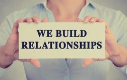 Affärskvinnan räcker det hållande kortet med oss bygger förhållandemeddelandet Arkivbilder