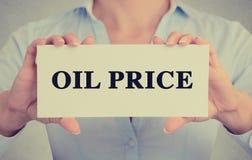 Affärskvinnan räcker det hållande korttecknet med oljepristextmeddelandet arkivfoto