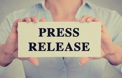 Affärskvinnan räcker det hållande korttecknet med pressmeddelandemeddelandet Royaltyfri Fotografi