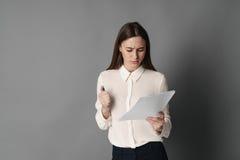 Affärskvinnan rymmer legitimationshandlingar i hennes händer och läser vad är skriftlig där på grå bakgrund Royaltyfri Foto
