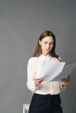 Affärskvinnan rymmer legitimationshandlingar i hennes händer och läser vad är skriftlig där på grå bakgrund Royaltyfri Bild