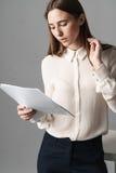 Affärskvinnan rymmer legitimationshandlingar i hennes händer och läser vad är skriftlig där på grå bakgrund Arkivfoto