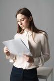 Affärskvinnan rymmer legitimationshandlingar i hennes händer och läser vad är skriftlig där på grå bakgrund Royaltyfria Bilder