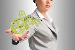 Affärskvinnan rymmer upp en mekanism av kugghjul Royaltyfri Bild