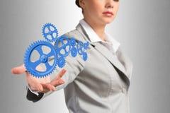 Affärskvinnan rymmer upp en mekanism av kugghjul Royaltyfria Bilder
