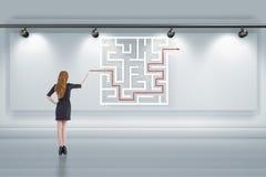 Affärskvinnan söker efter vägar att fly från labyrintlabyrint arkivfoton