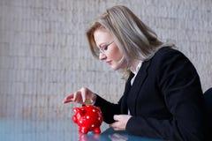 Affärskvinnan satte mynt in i spargrisen Arkivbilder