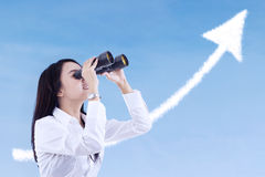 Affärskvinnan ser framgångmolnet med kikare Arkivbild