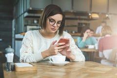 Affärskvinnan sitter i coffee shop på tabellen och använder smartphonen som arbetar E-lära hipsterflicka fotografering för bildbyråer