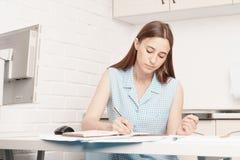 Affärskvinnan sitter på hans skrivbord och skriver i en anteckningsbok Fotografering för Bildbyråer