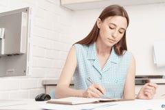 Affärskvinnan sitter på hans skrivbord och skriver i en anteckningsbok Arkivfoton