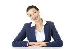 Affärskvinnan sitter på skrivbordet Royaltyfri Fotografi