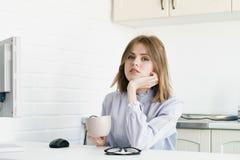 Affärskvinnan sitter på skrivbordet med en kopp En i kontoret i vindstilen Arkivbild