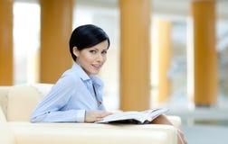 Affärskvinnan sitter på sofaen med boken Royaltyfri Bild