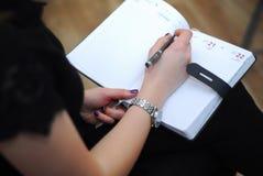 Affärskvinnan skriver anmärkningar i en anteckningsbok Arkivfoton