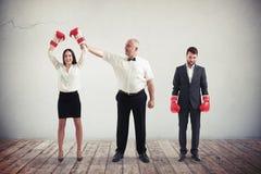 Affärskvinnan slår affärsmannen i boxningmatch Arkivbilder