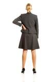 Affärskvinnan som är stående i säkert, poserar tillbaka Arkivfoto