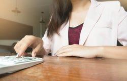 Affärskvinnan som analyserar investering, kartlägger med räknemaskinlapto royaltyfria foton