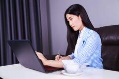 Affärskvinnan som arbetar med bärbar datordatoren och, skriver en tidskrift arkivbilder