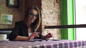 Affärskvinnan som arbetar med en minnestavla och, jublar i kafé 4K lager videofilmer