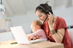 Affärskvinnan som arbetar på bärbara datorn med henne, behandla som ett barn Arkivbild