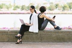 Affärskvinnan som arbetar på sammanträdet för bärbar datordatoren nära den avslappnande sportkvinnan i stad, parkerar royaltyfri bild