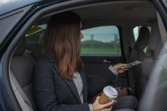 Affärskvinnan som betalar med chauffören och, ordnar till för att lämna bilen Royaltyfria Bilder
