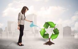 Affärskvinnan som bevattnar gräsplan, återanvänder teckenträdet på stadsbackgrou Royaltyfria Bilder