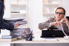Affärskvinnan som får mer för att arbeta under upptagen tid fotografering för bildbyråer