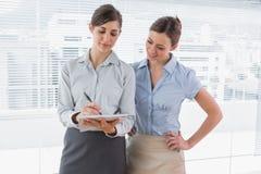 Affärskvinnan som håller ögonen på hennes kollega, skriver på skrivplattan Arkivfoton