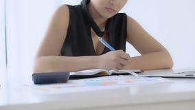 Affärskvinnan som har bärbar datordatoren på skrivbordet, beräknar kostnader och att skriva anmärkningsboken med besparingfinans  arkivfilmer