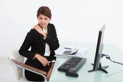Affärskvinnan som har skuldran, smärtar på datorskrivbordet Arkivbilder