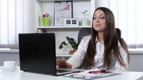 Affärskvinnan som i regeringsställning sitter framme av en bärbar dator och talar på en webcam, är lycklig och att le arkivfilmer