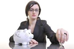 Affärskvinnan som sätter pengar, coins i den piggy gruppen Royaltyfri Fotografi