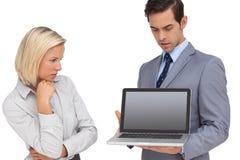 Affärskvinnan som ser bärbara datorn, rymde vid hennes kollega Arkivbild