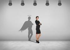 Affärskvinnan står med skugga på väggen arkivbild