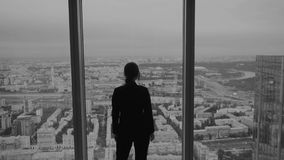 Affärskvinnan står nära ett stort fönster på ett högt golv av en skyskrapa arkivfilmer