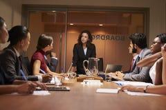 Affärskvinnan står tilltala laget på mötet, låg vinkel royaltyfri fotografi