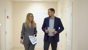Affärskvinnan talar med en partner som går ner korridoren lager videofilmer