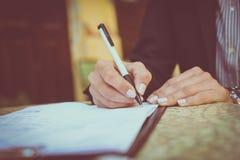 Affärskvinnan undertecknar in dokument close upp royaltyfri bild