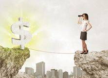 Affärskvinnan vaggar på berget med en dollarfläck Royaltyfria Foton