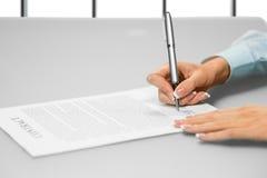 Affärskvinnans hand undertecknar ett dokument arkivbild
