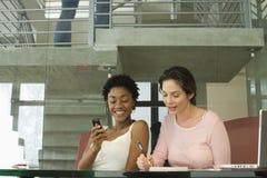 AffärskvinnaOn Call With kvinnlig kollega som ner noterar royaltyfri bild