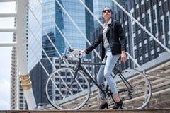 Affärskvinnaridningcykel som arbetar på den stads- gatan i stad transport och sunt den kalla modelivsstilen ilar arkivfoto