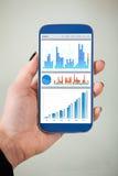 Affärskvinnas analyserande diagram på smartphonen Arkivbild
