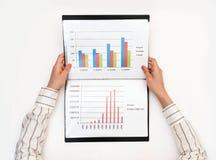 Affärskvinnas händer som rymmer en mapp med diagram på en vit tabell arkivfoto