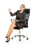 Affärskvinnasammanträde på en stol och peka Arkivbild