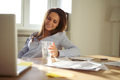 Affärskvinnasammanträde på skrivbordet i hennes inrikesdepartementet Fotografering för Bildbyråer